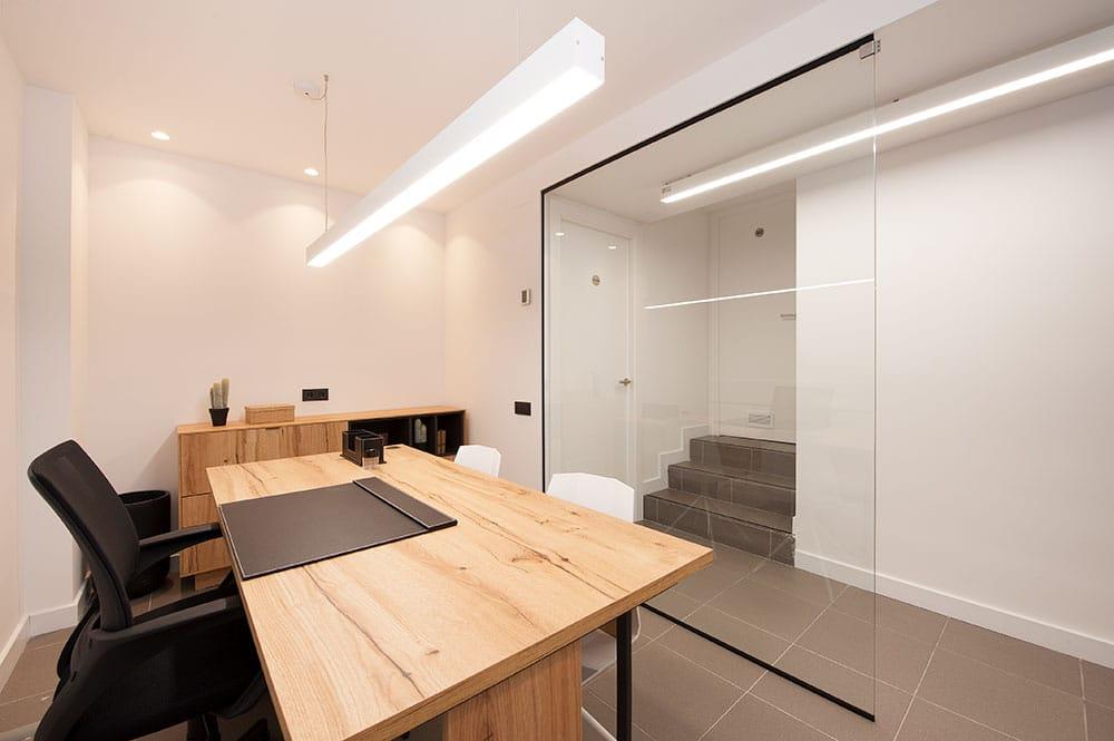 Despacho estilo nórdico con paredes de cristal.