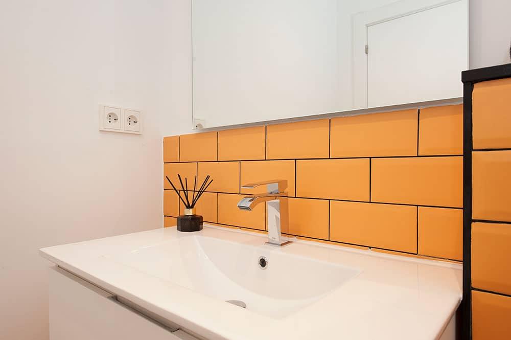 Lavabo con baldosas tipo metro amarillo naranja con juntas negras. Reformas Sincro.