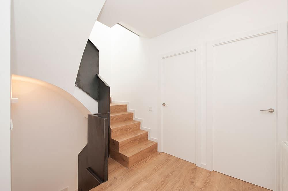 Escalera interior dúplex revestimiento de madera y barandilla de hierro oscuro.