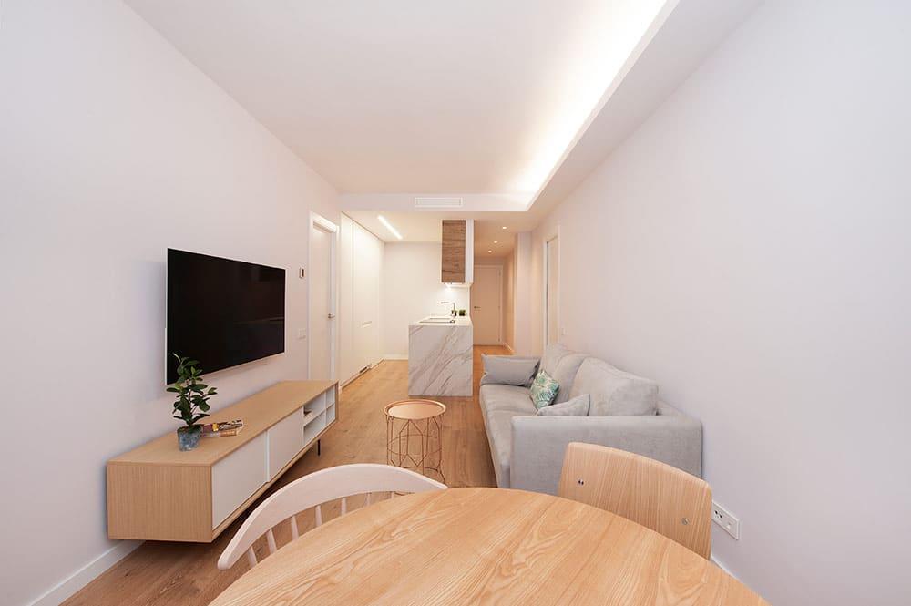 Salón de estilo nórdico minimalista con cocina abierta