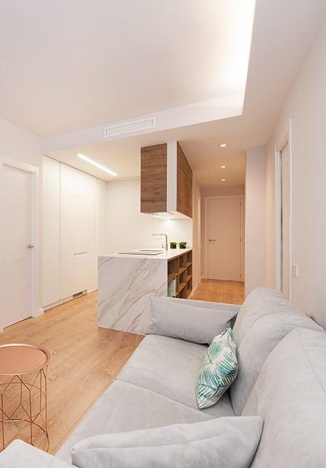 Sala de estar con cocina blanca y madera