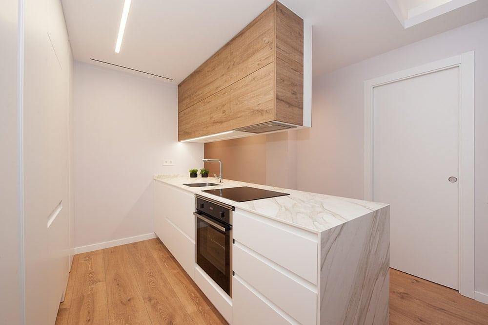 Cocina con mueble bajo color blanco y sobre mueble de madera. Encimera de marmol blanco.