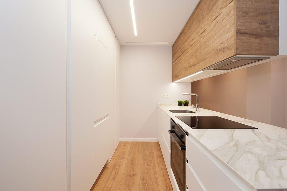 Península de cocina con encimera de marmol y mobiliario blanco y madera.