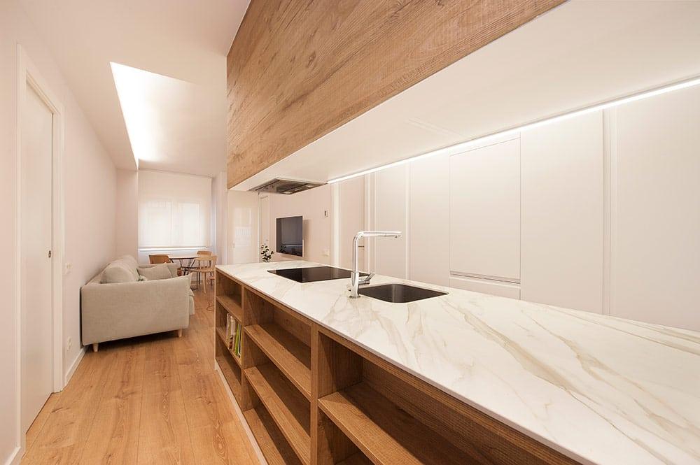 Mobiliario de madera en cocina combinado con mármol y lacado blanco