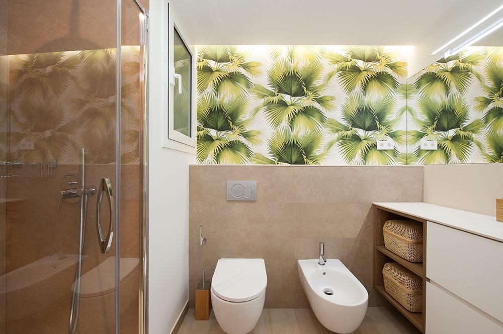 Papel pintado patrones de hojas de palmera en una pared del baño reformado por el equipo de Sincro.