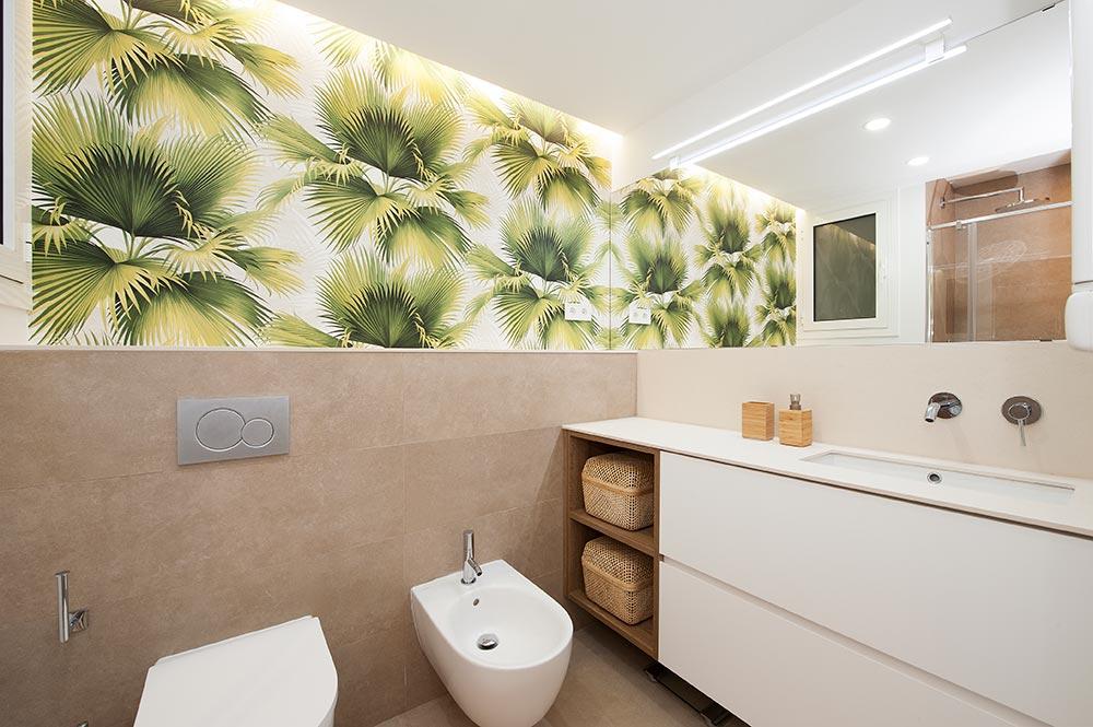 Cuarto de baño con papel pintado de hojas. Reformas de baño Sincro.