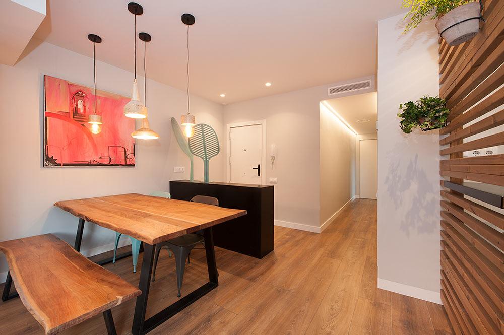 Mesa de comedor con banco de madera y lamparas colgantes