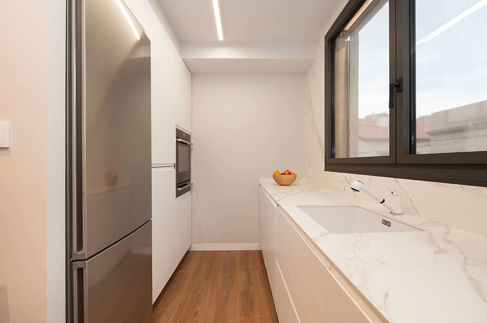 Cocina blanca en galera de color blanca. Reforma Sincro