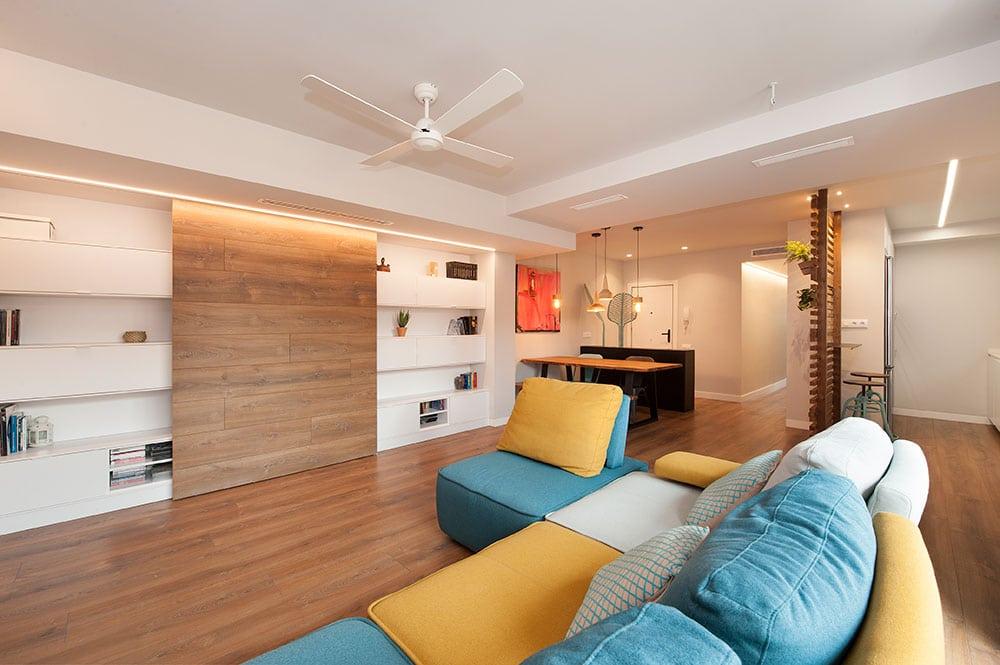 Sala de estar abierta moderna y con toques de color. Sofá y mueble tv.