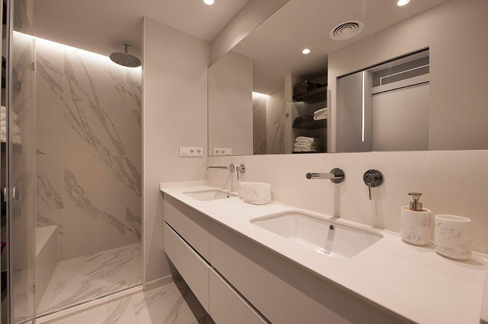 Lavabo con dos picas en color blanco. Revestimientos marmol imitación.