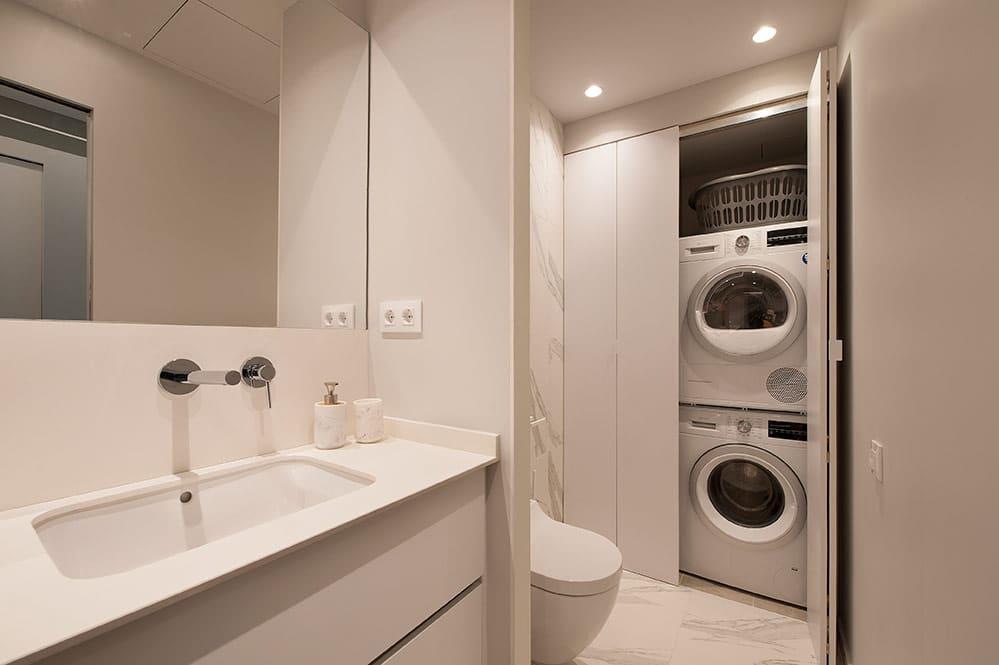 Lavandería en el cuarto de baño oculto por en un armario con puertas correderas.