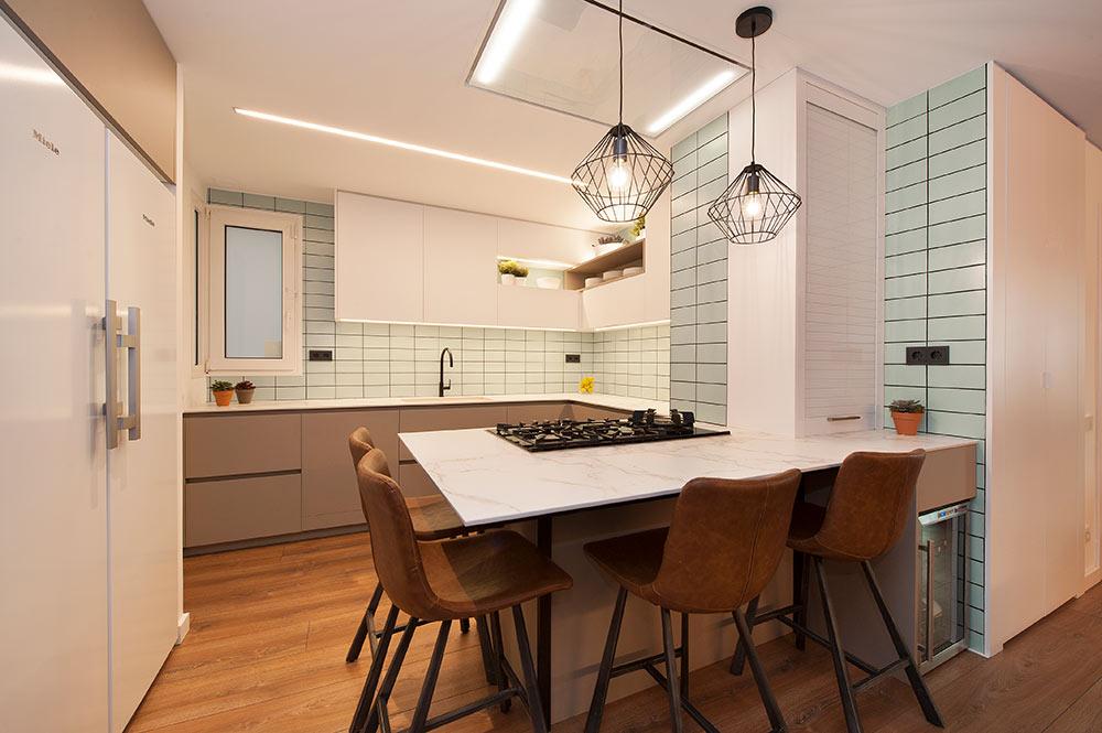 Cocina de color blanco y verde suave con barra en la península. Reforma de cocinas Sincro.