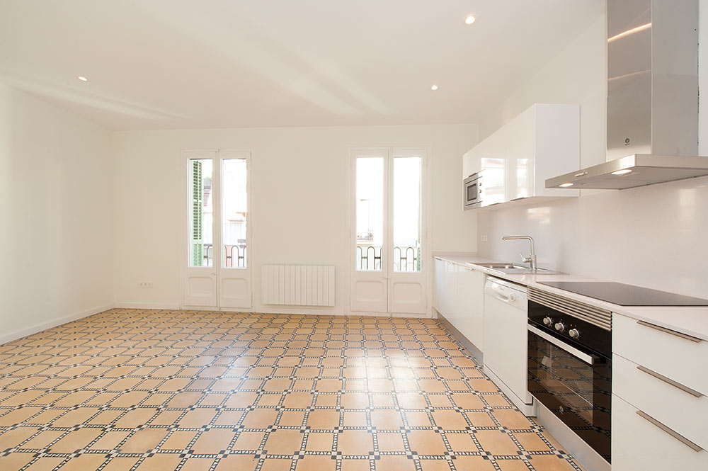 Salón con cocina lineal en un piso que se ha rehabilitado para alquilar en Barcelona.