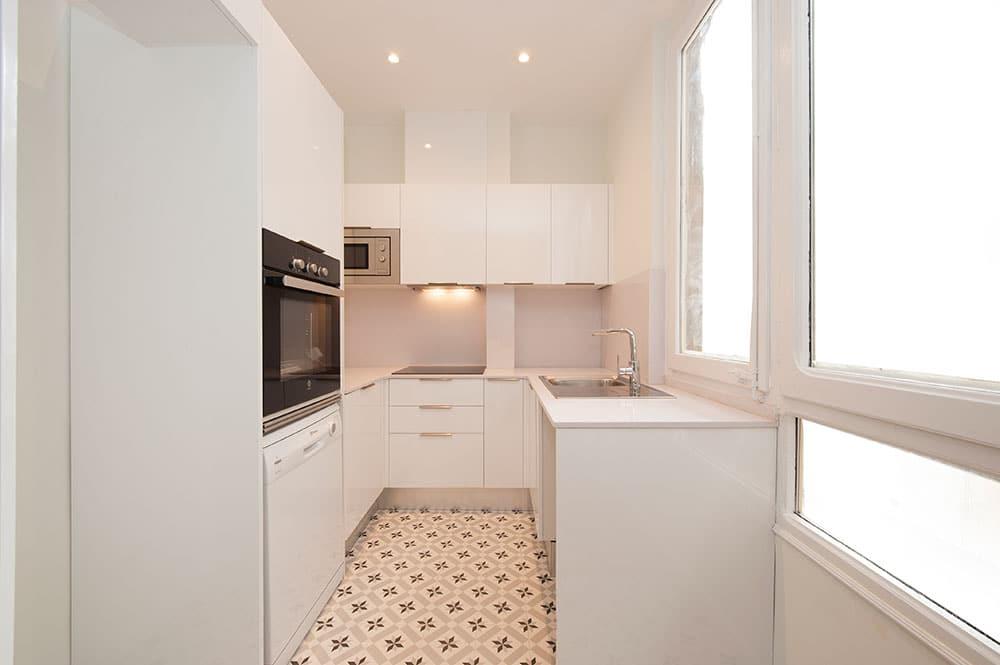 Cocina de color blanco en forma de U. Piso reformado para alquiler.