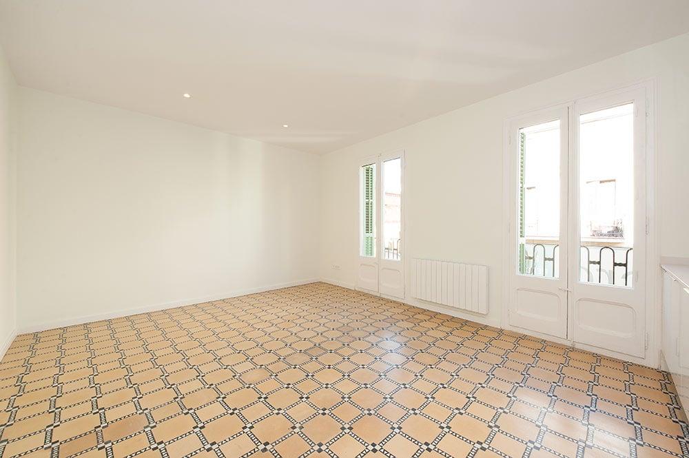 Rehabilitación salón piso antiguo para alquilar. Salón con pavimento baldosa hidráulica y ventanas de madera.