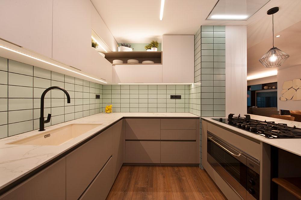 Cocina con baldosas rectangulares verde suave juntas negras. Distribución en U. Reforma Sincro.