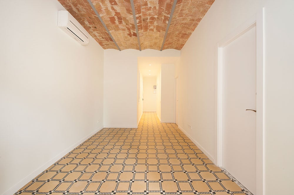 Rehabilitación piso para alquiler. Salón con techo bóveda catalana y suelo hidráulico. Reforma Barcelona Sincro.