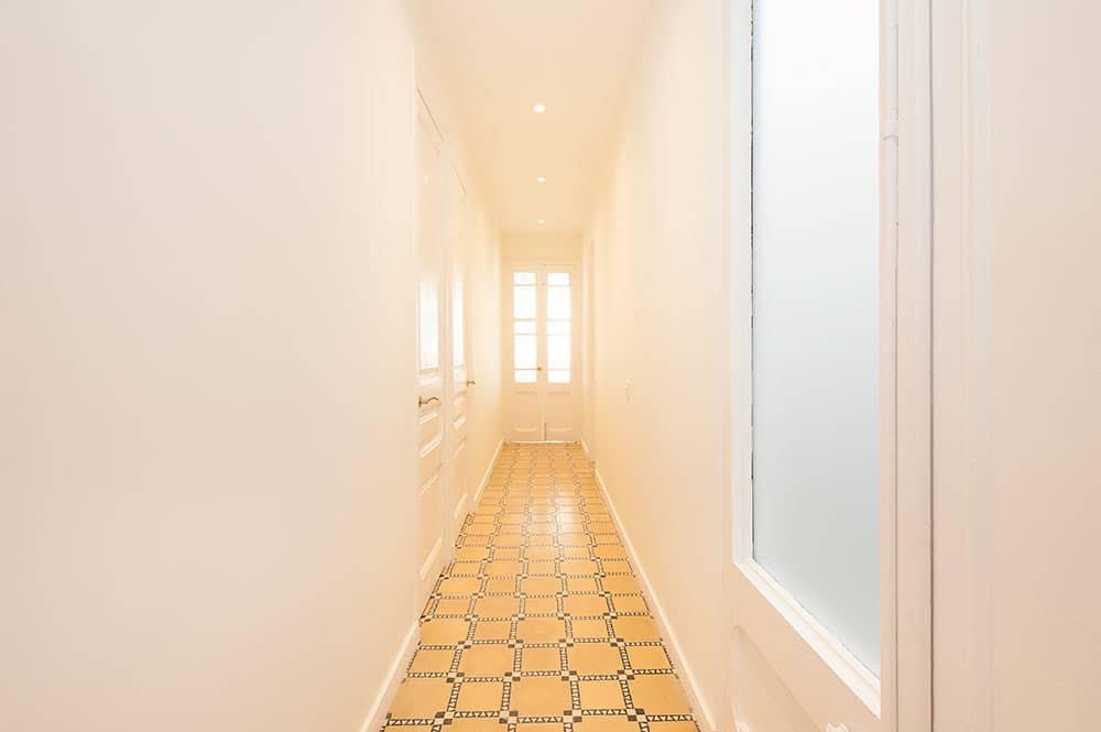 Pasillo con puertas y pavimento restaurado en un piso alquiler. Sincro rehabilitaciones.