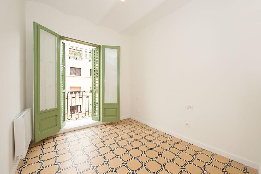 Ventanas y porticones en dormitorio restaurados en color verde y blanco. Rehabilitación piso alquiler Barcelona.