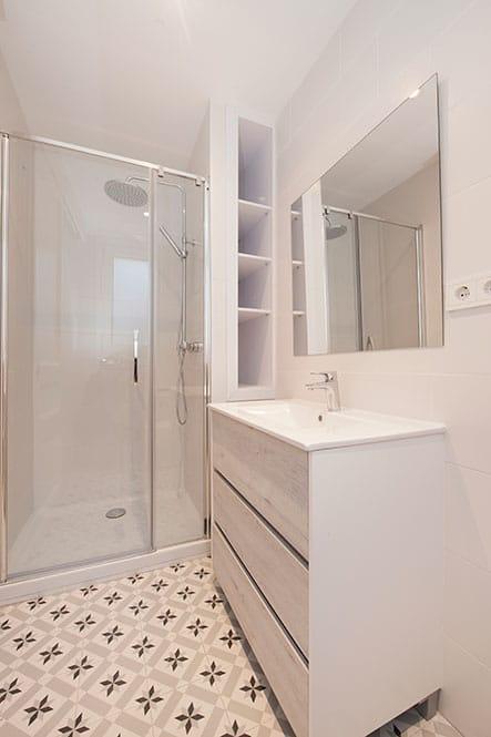 Cuarto de baño tonos blancos con suelo mosaico