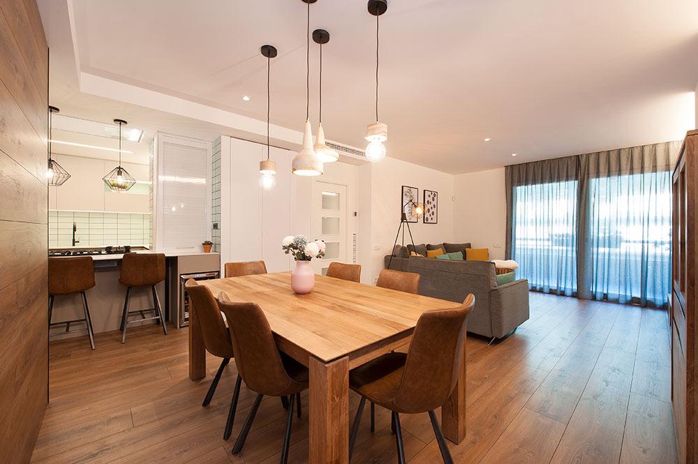 Comedor con mesa de madera, sillas de piel marrones y lámparas de techo colgantes. Sincro interiorismo.