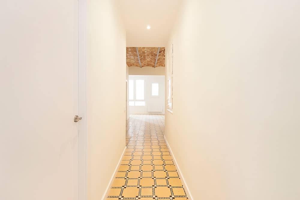 Pasillo con baldosas hidráulicas restauradas. Reforma para piso de alquiler en Barcelona.