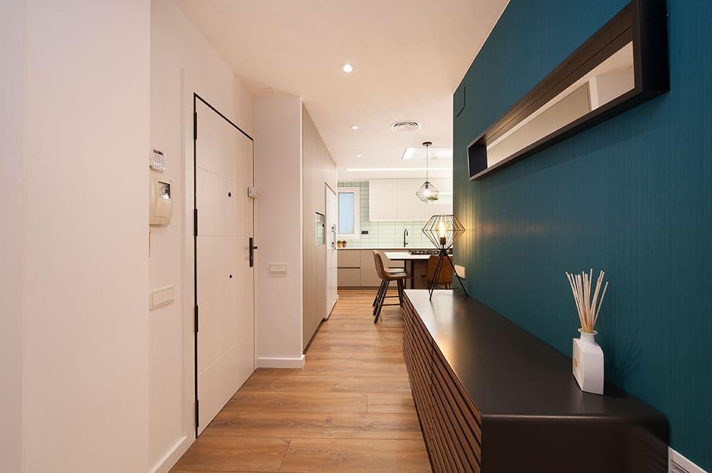 Recibidor con mueble madera y negro, y pared con revestimiento vescom azul oscuro. Diseño Sincro