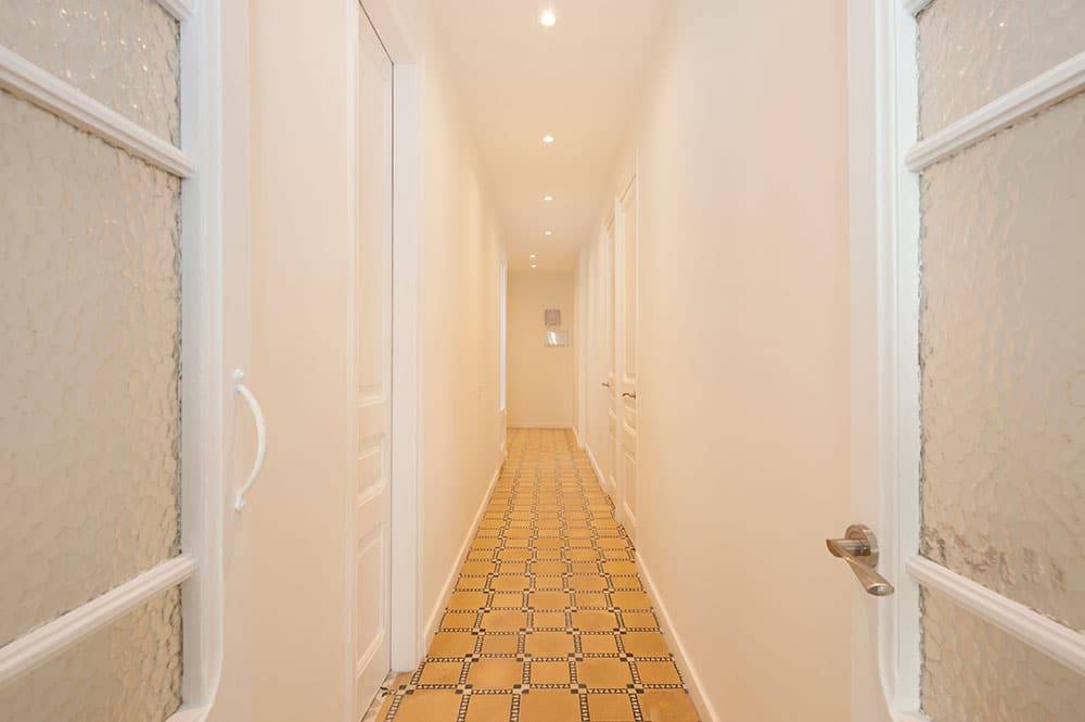 Pasillo reformado en piso alquiler. Suelo hidráulico y paredes blancas.