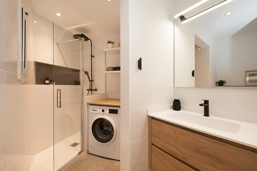 Baño estilo nórdico con baldosas tipo metro blanco, lavabo de madera y grifería en negro. sincro