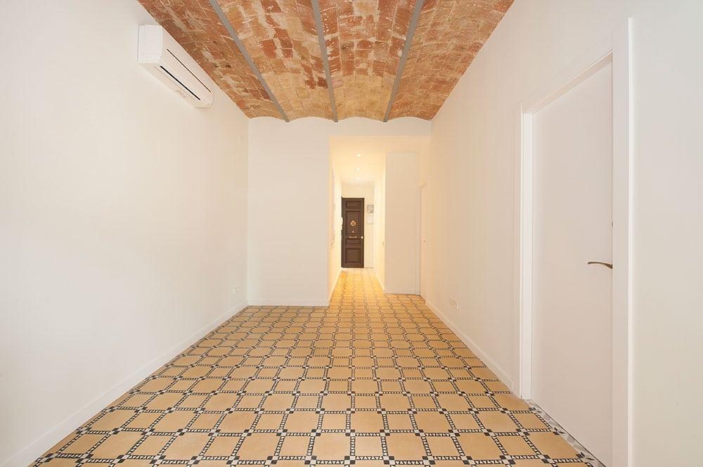 Salón sin amueblar y pasillo rehabilitado. Suelo baldosa hidráulica y techo bóveda catalana.