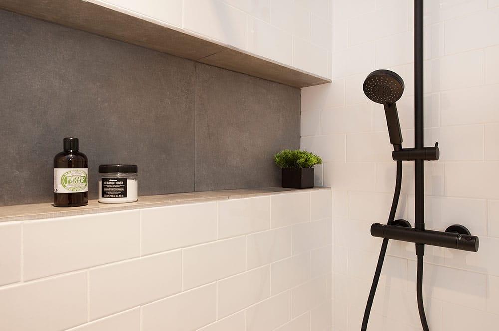 Hornacina pared en gris en la ducha. Grifería en negro. Bladosa metro blanca.