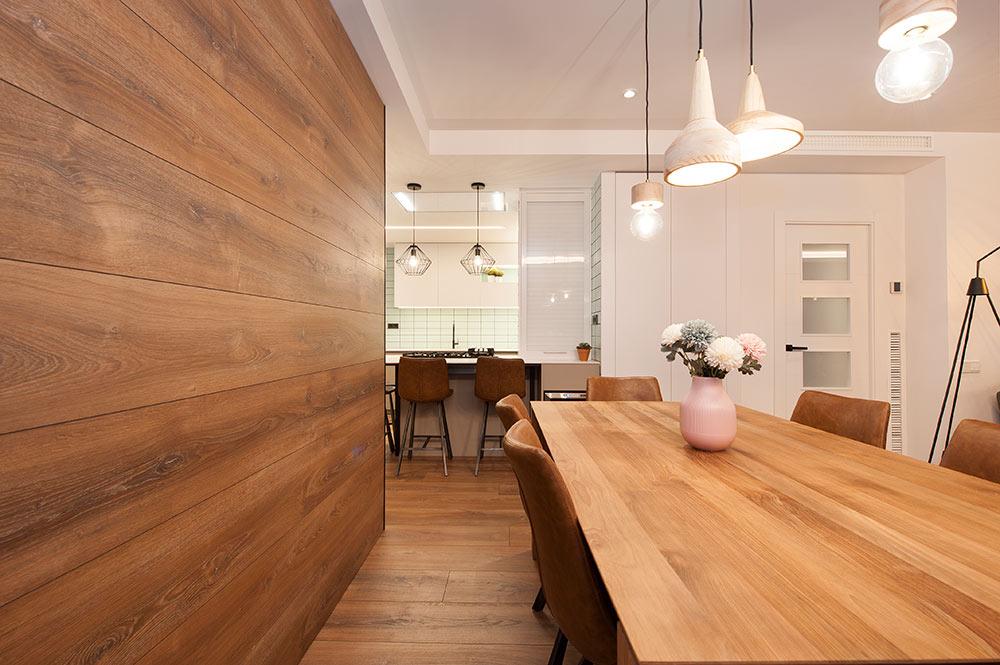 Puerta corredera revestida con el mismo material del parquet de la vivienda. Diseño interior Sincro.