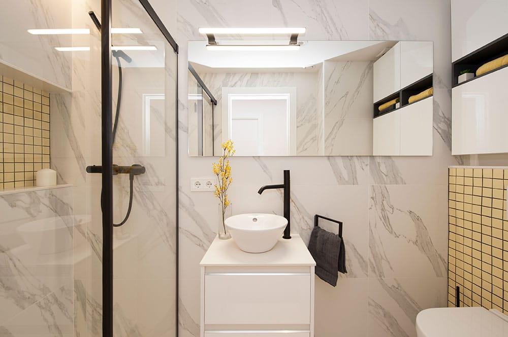 Cuarto de baño pequeño con imitación mármol blanco y toques de color amarillo. Reforma Sincro.