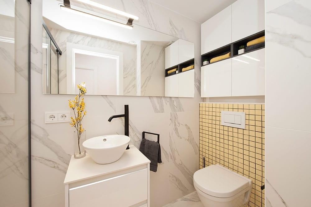 Cuarto de baño con mármol blanco, mosaico en amarillo y grifería en negro.