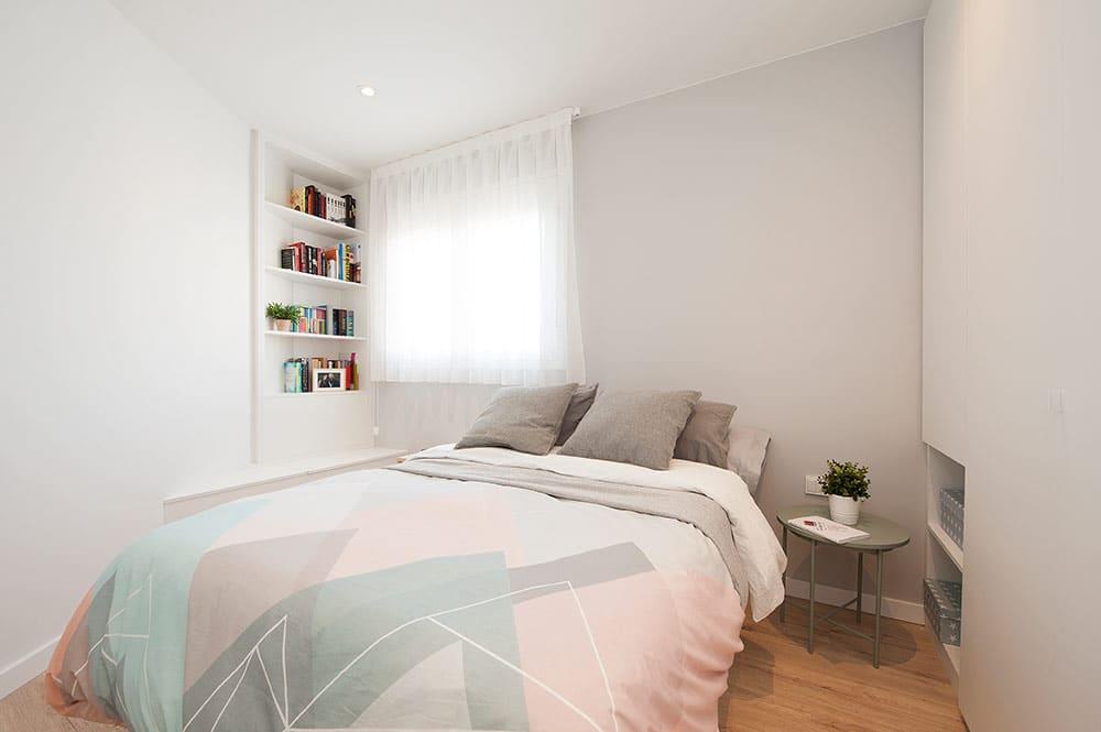 Mueble rinconero con librería y banquillo en dormitorio principal.
