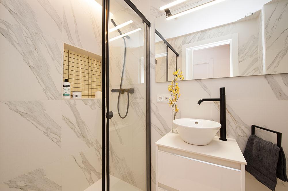 Baño con perfiles mampara y grifería en negro, revestimientos imitación mármol blanco. Hueco con mosaico color amarillo.