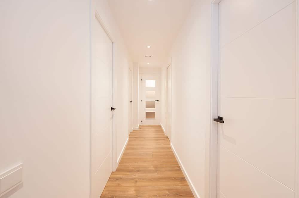 Pasillo reformado color blanco, suelo parquet y manillas puertas en negro.