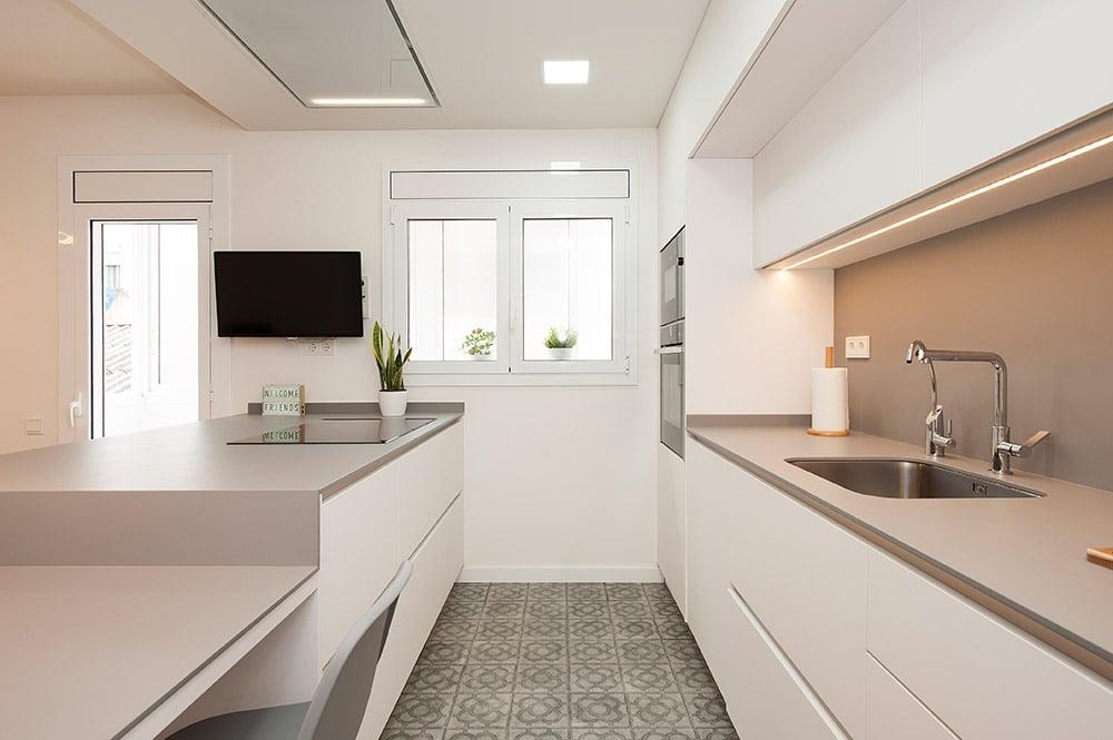 Cocina con mobiliario distribuido en paralelo. Suelo con panots del pavimiento Barcelona