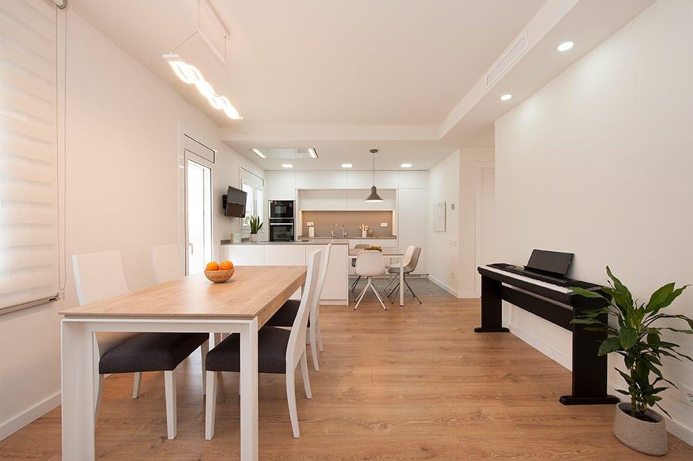 Vista del comedor y de la cocina. Piano en una de las paredes.