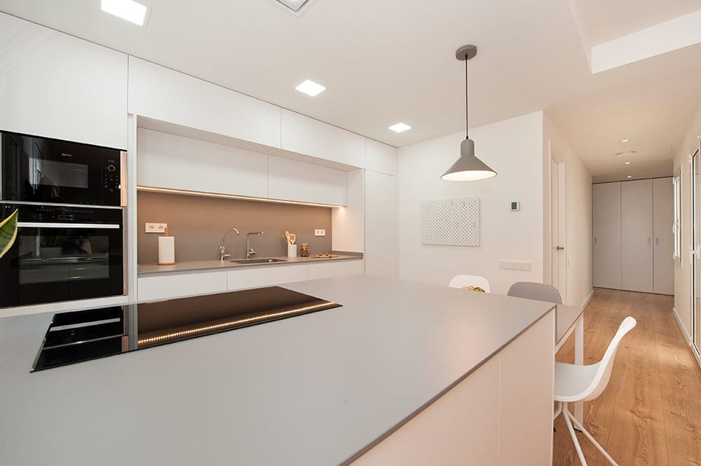 Cocina open concept de color blanco y gris.