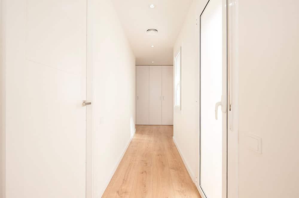 Pasillo blanco con suelo de parquet madera claro