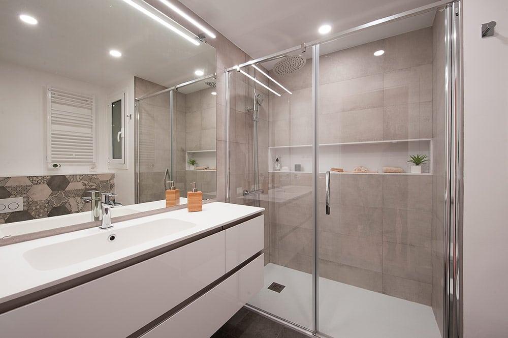 Baño con hueco longitudinal en la pared de la ducha. Colores grises y blanco.
