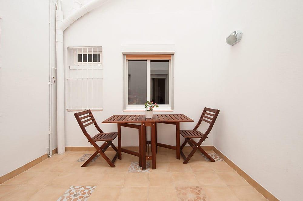 Patio interior grande con mesa y sillas
