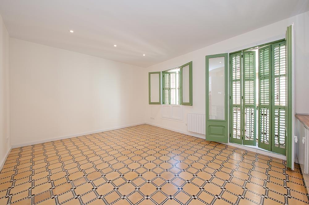 Ventana y balconeras con porticones en verde restauradas. Rehabilitación piso Barcelona