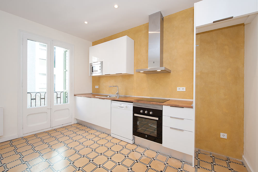 Cocina blanca con pared de microcemento anaranjado