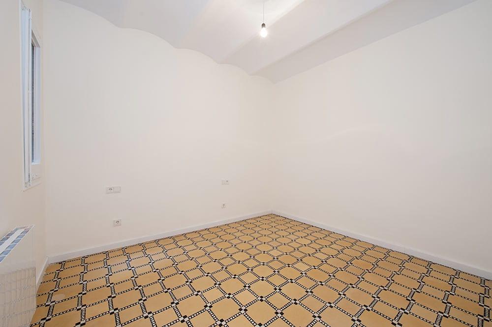 Habitación vacía con suelo hidráulico. Piso para alquilar.