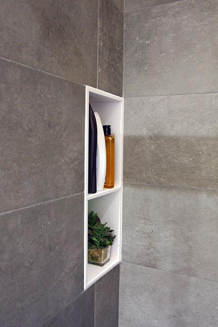 Hornacina en vertical con un estante. Situado en un rincón de la ducha.