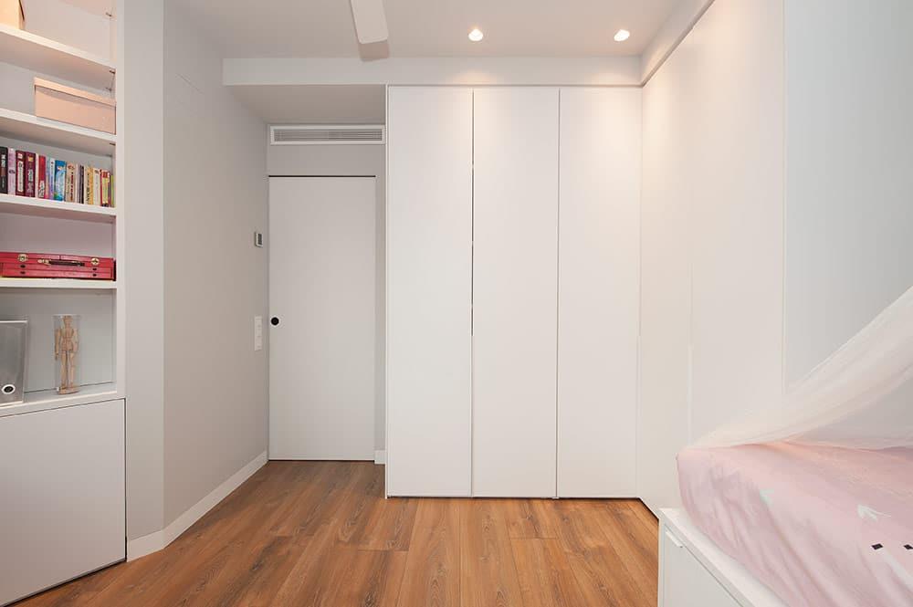 Porta corredissa encastada a la paret en dormitori infantil. sincro