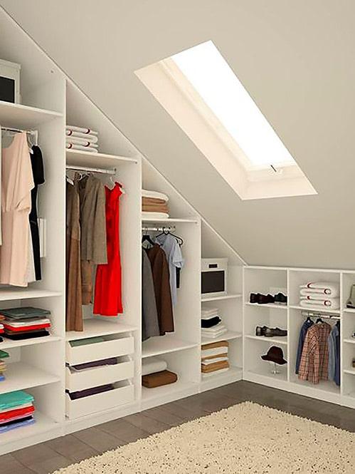 vestidor con armario empotrado abierto bajo techo inclinado en una buhardilla
