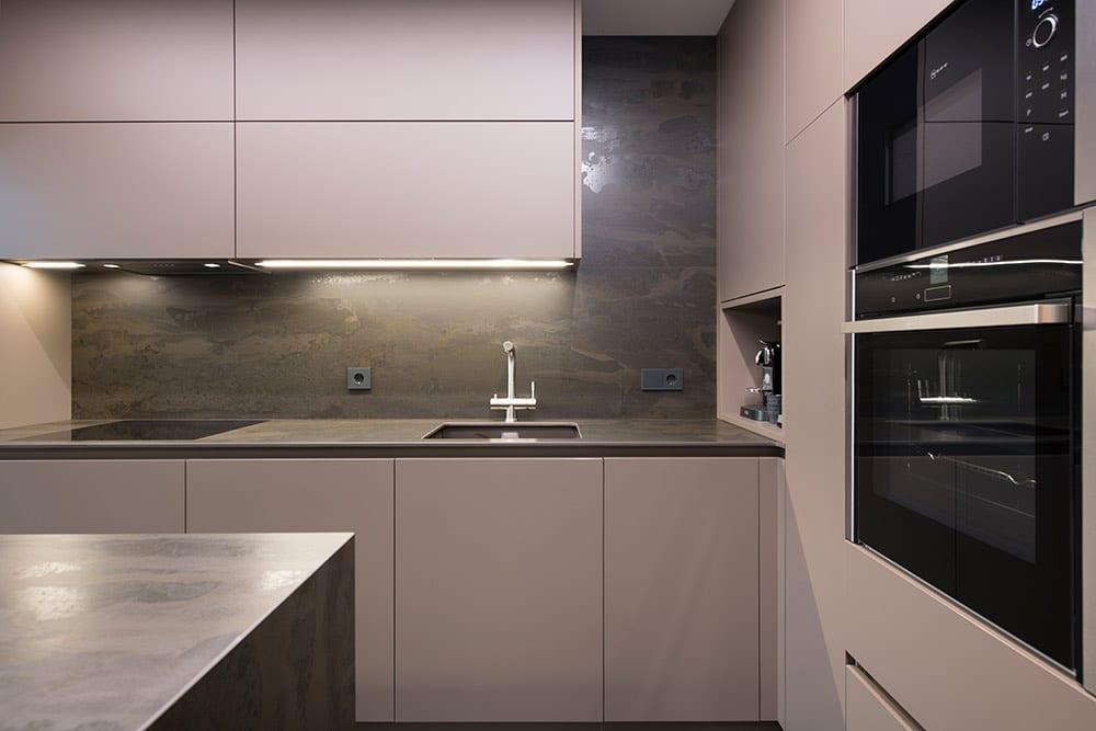 Cocina con mobiliario color arcilla y encimera de efecto óxido